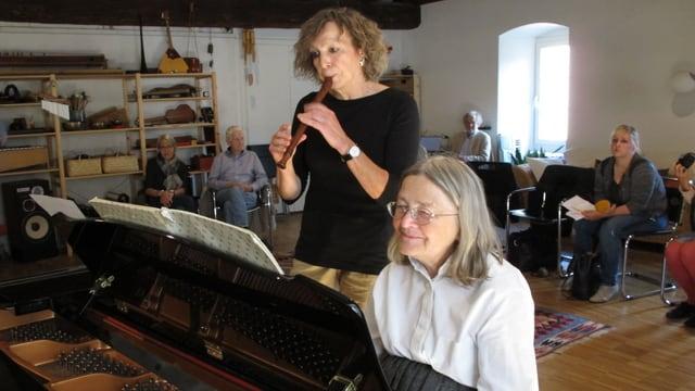 Eine Frau spielt stehend Blockflöte, rechts neben ihr sitzt eine ältere Frau mit grauen Haaren am Klavier.