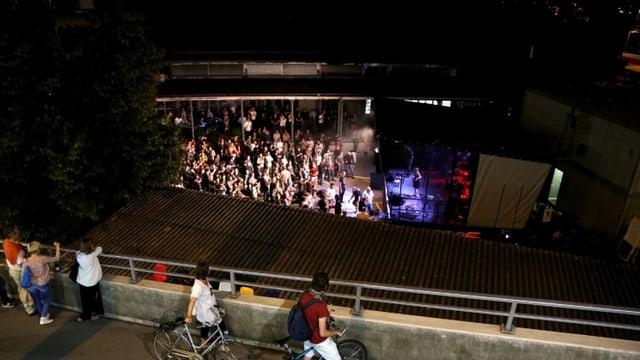 Passanten blicken von der Hardbrücke hinunter zum Helsinki, wo ein Konzert über die Bühne geht.