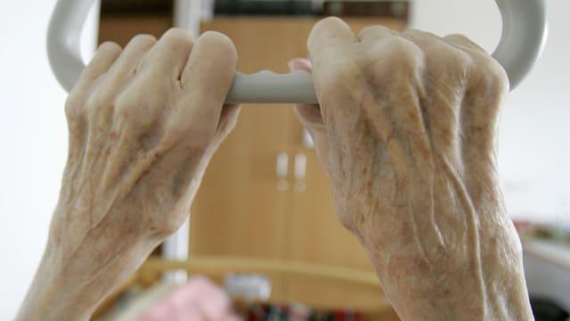 Die Hände einer älteren Frau am Griff eines Spitalbetts