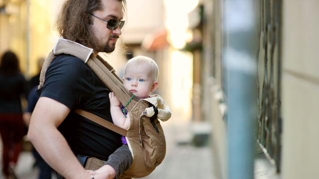 Ein Mann mit langen Haaren und Sonnenbrille trägt einen kleinen Jungen im Tragtuch auf dem Bauch.