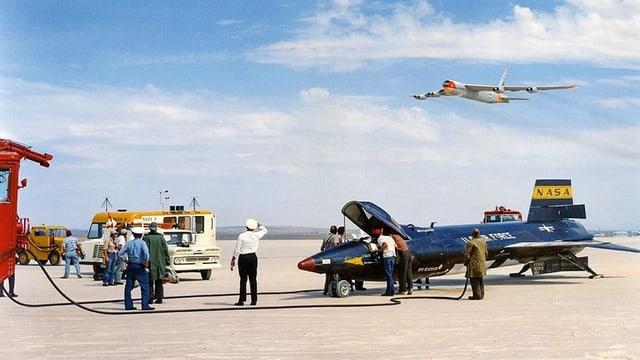 Ein Spaceshuttle ist in der Luft und fliegt über einen Flugplatz, auf welchem ein weiteres Flugobjekt steht, an welchem gerade Mechaniker arbeiten.