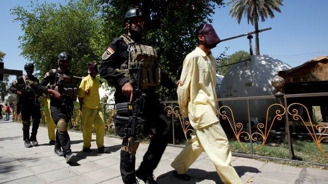 Irakische Polizisten führen mutmassliche IS-Kämpfer ab.