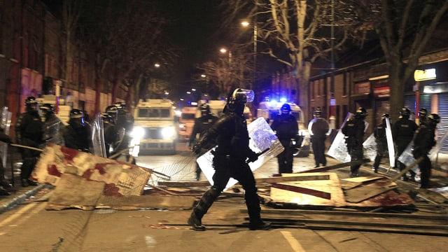 Mit Transparent-Tafeln blockierte Strasse in der Nacht. Polizisten mit Schlagstöcken kontrollieren die Situation.