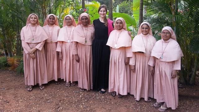 Deborah Sutter und sieben orange gewandete Nonnen