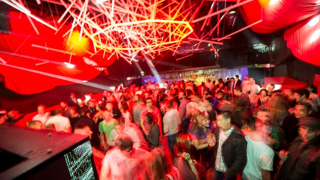 Eine Disco mit roter Deckenbeleuchtung, viele Menschen auf der Tanzfläche.