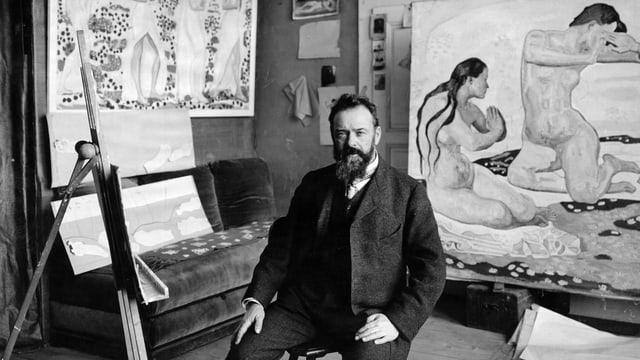 Ein Mann sitzt in seinem Atelier, umringt von Bildern