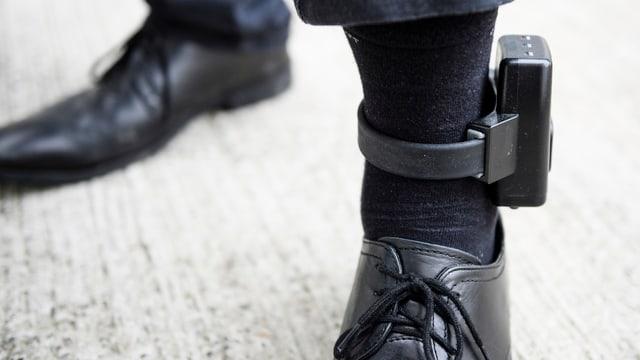 Zwei Männerbeine, das Eine trägt über den schwarzen Socken eine elektronische Fussfessel.