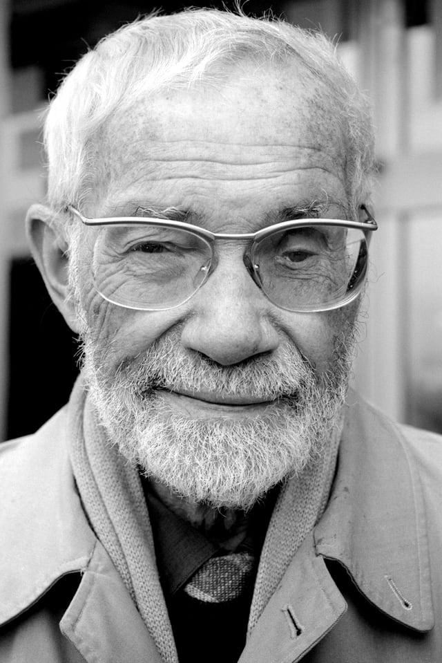 Schwarweiss Bild eines weisshaarigen Mannes mit Brille und Mantel.