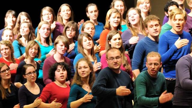 Viele junge Menschen, die zusammen singen. Sie machen alle eine eigenartige Bewegung mit der Hand; eine Choreografie zum Singen.