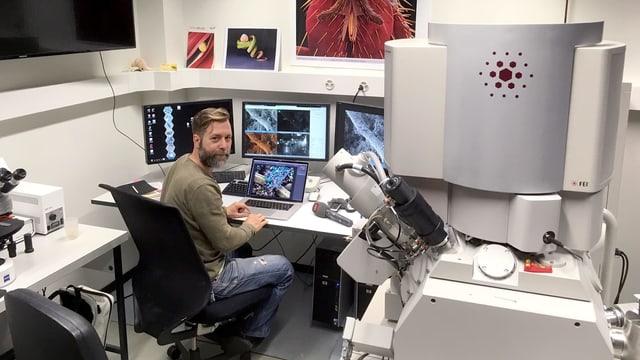 Ein Mann sitzt an einem Tisch mit mehreren Screens, daneben ein Mikroskop.