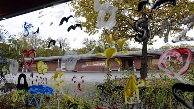 Eine von Kindern bemalte Fensterscheibe mit Blick auf den Innenhof.
