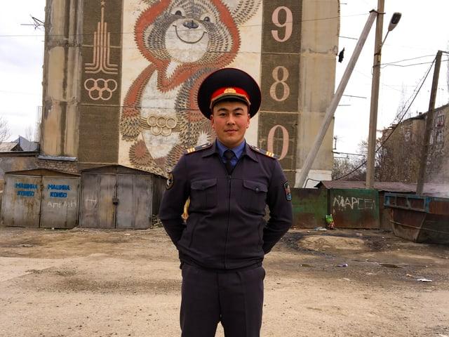 Beamter vor einer Hauswand, die verziert ist mit dem Logo der olympischen Spiele aus Zeiten der Sowjetunion