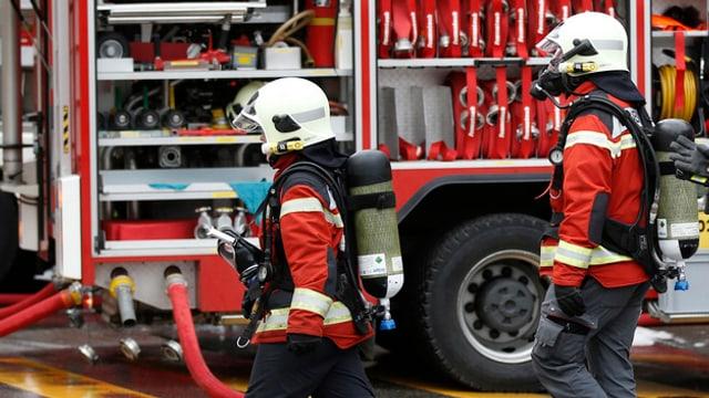 Atemschutz-Feuerwehrleute vor einem Fahrzeug