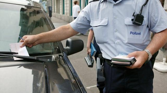 Polizist erteilt eine Parkbusse.