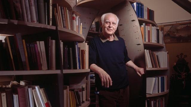 Ein Mann steht zwischen Büchergestellen
