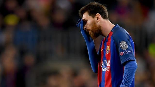 Lionel Messi hält die Hand vor das Gesicht