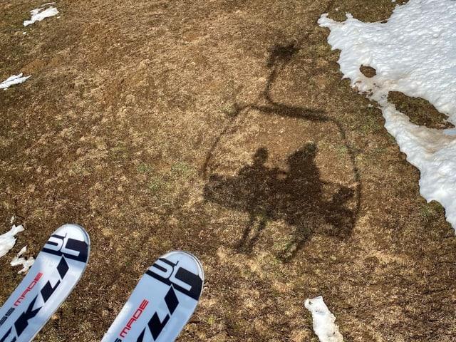 Skifahrer auf Sessellift vor aperer Wiese
