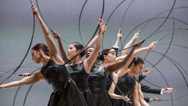 Tänzerinnen halten Stahlreifen in die Luft.