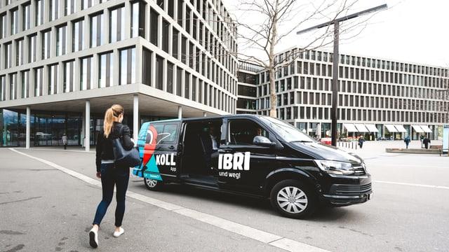 Schwarz-blauer Minivan vor Hochhäuser.