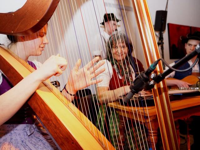 Eine Frau spielt Harfe, eine Frau spielt Hackbrett und ein junger Mann spielt Gitarre.