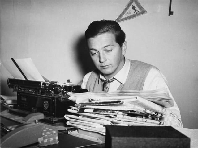 Sepp Renggli 1953 mit Bergen von Zeitungen und einer mechanischen Schreibmaschine im Radiostudio Zürich.