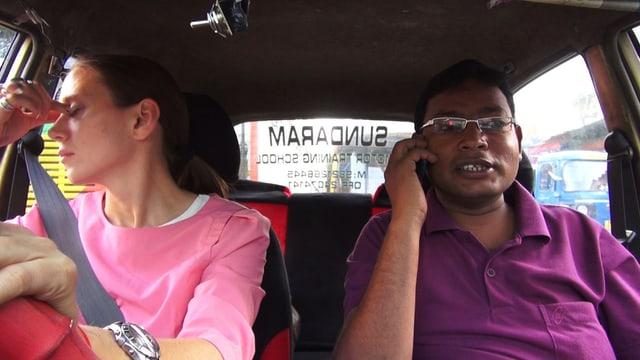 Eine Frau sitzt mit einem Mann im Auto. Er ist Inder und telefoniert. Sie ist Deutsche und hält ihre Hand an die Stirn.