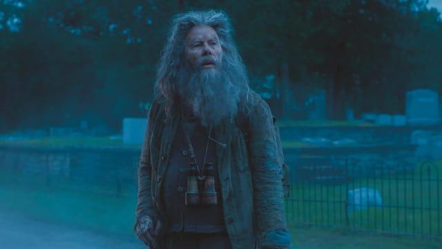 Ein Zombie mit grauen langen Haaren und langem grauen Bart.