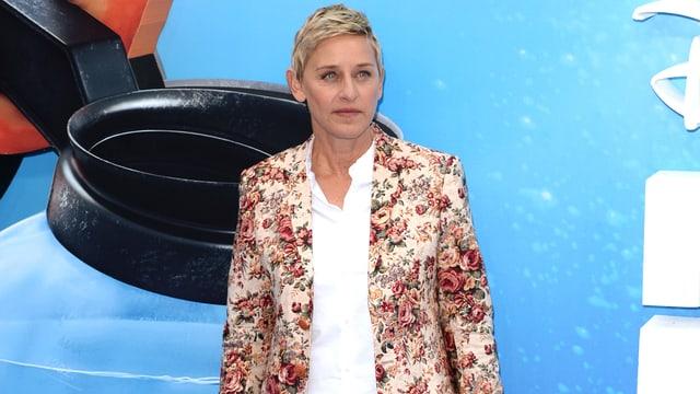 Ellen DeGeneres posiert vor einem Plakat.