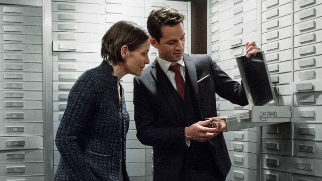 Ein Mann öfnnet in einem Tresorraum ein Bankenschliessfach und zeigt den Inhalt einer Frau, die daneben steht.