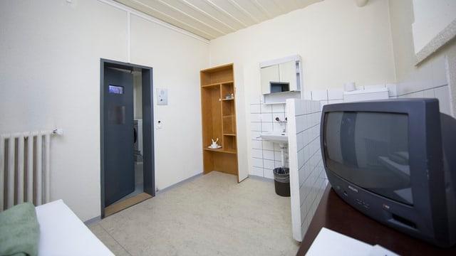Gefängniszelle mit Bett, TV, Einbaugestellt und kleiner Nasszopne.