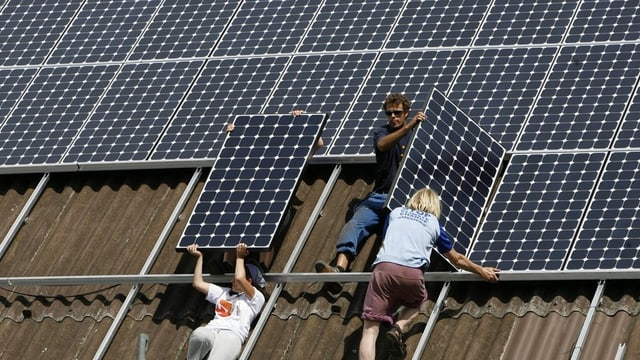 Jugendliche montieren Solarzellen auf einem Scheunendach.