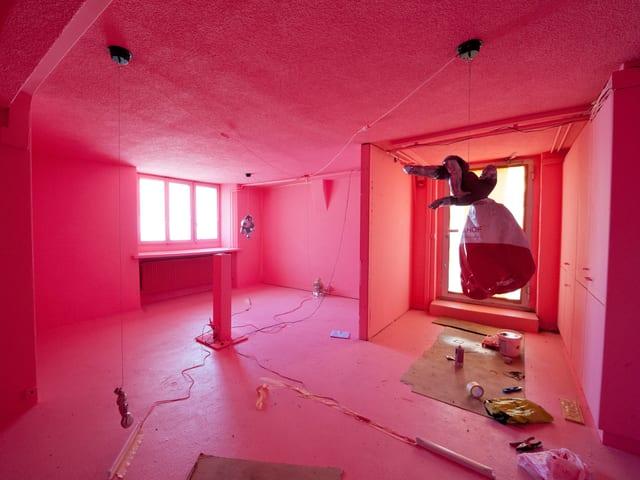 Ein mit Pink ausgeleuchteter Raum, in dem Puppen und nicht klar definierbare Objekte an Schnüren aufgehängt sind und am Boden liegen.