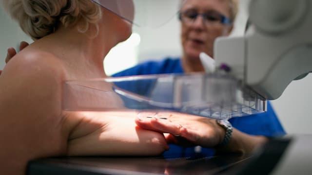 Einer Frau wird die Brust untersucht: Ihre rechte Brust liegt auf einem Gerät und wird mit Licht beschienen, Ärztin hält Hand darüber, scheint Brust richtig zu plazieren.