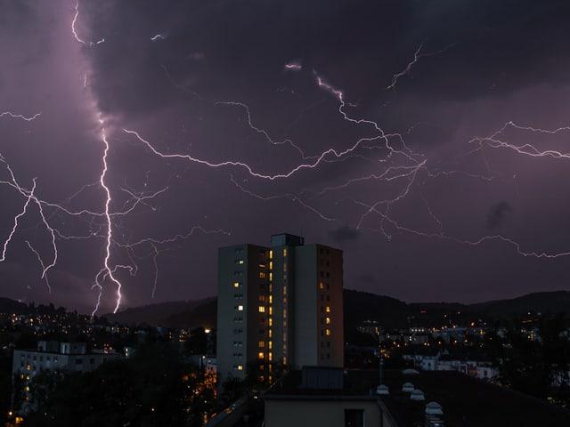 Viele Blitze erhellen den Himmel über einer Stadt.