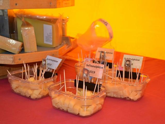 Vier kleine Behälter mit Käsestücken.
