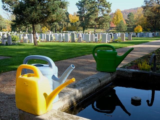 Gieskannen auf einem Brunnen, im Hintergrund Gräber