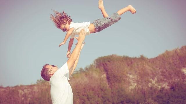 Ein Mann wirbelt ein Mädchen durch die Luft.