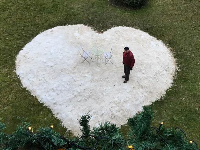 Ein Mann steht auf einem Herz aus Schnee