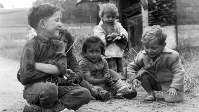 Ein Gruppe von etwas verwahrlosten Kindern sitzt lachend auf der Strasse.