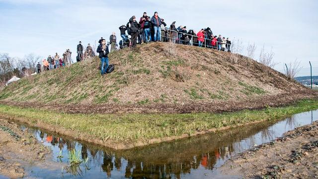 Menschen mit Kameras stehen auf einem Hügel