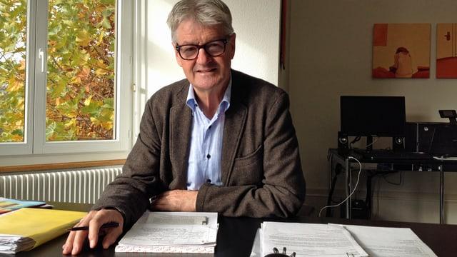 Franz Arnold, Gemeindepräsident von Spiez, sitzt in seinem Büro vor einem Stapel Papiere.