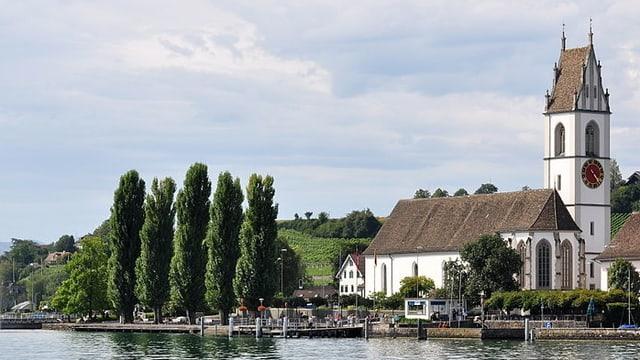 Eine Kirche steht nah am Wasser, links davon vier spitze grüne Bäume.