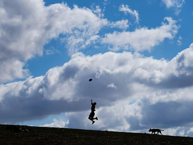Ein Fussballer trainiert allein mit seinem Hund.