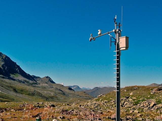 Wetterstation mit verschiedenen Instrumenten in bergigem Gelände.