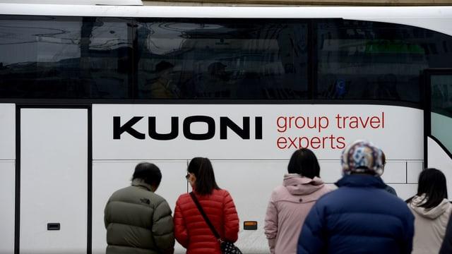 Reisebus mit Auschrift Kuoni, davor von hinten fotografiert wartende Reisende