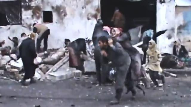 Chaos vor einem zerstörten Gebäude, im Hintergrund zahlreiche Tote.
