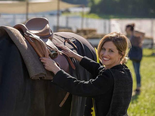 Frau steht neben einem gesattelten Pferd