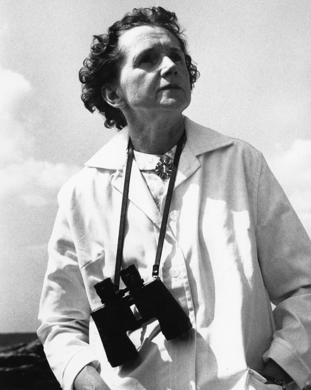 Schwarz-Weiss Bild einer Frau mit Feldstecher um den Hals hängend