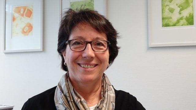 Porträt einer Frau mit Brille und beigem Fular