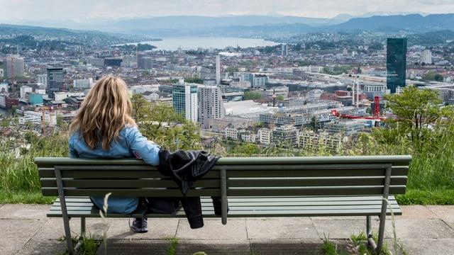 Ein Frau sitzt auf einer Bank und blickt von der Waid über die Zürich. Im Hintergrund wartet das Alpenpanorama auf. (keystone)